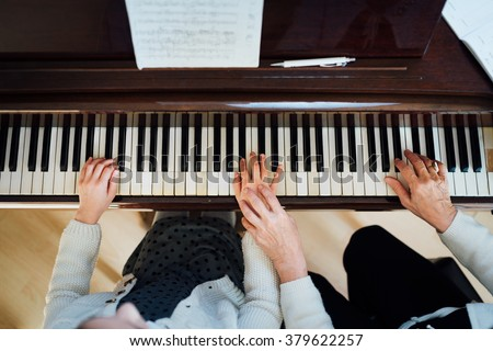 a music teacher with the pupil at the lesson piano, top view - stock photo