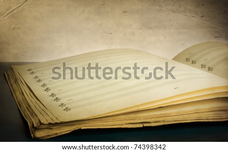 A musical composition book opened to a blank page against a grungy vintage texture - stock photo