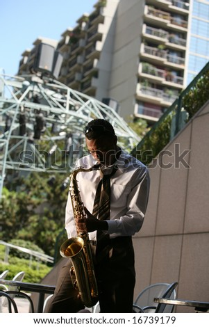 a musician plays his saxaphone for all to hear and enjoy - stock photo
