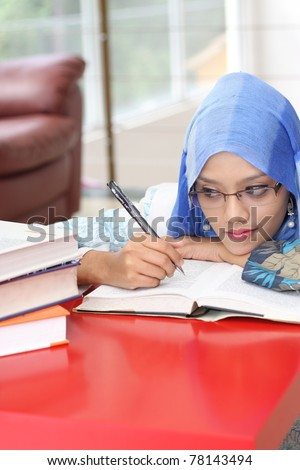 A muslim woman reading a book while looking at the book on the table - stock photo