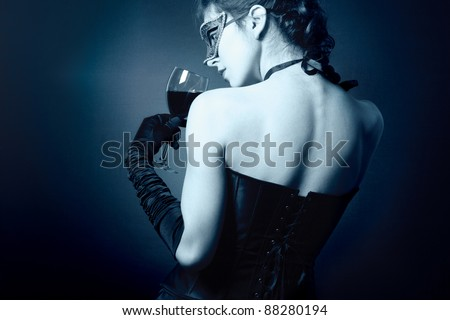 A mysterious young woman in carnival mask and a glass of red wine. - stock photo