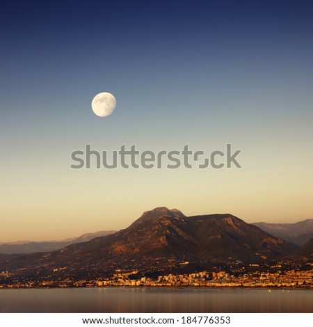 A Mythical Moonrise Over Mountains And Water As Sunset Gives Way To Twilight - stock photo