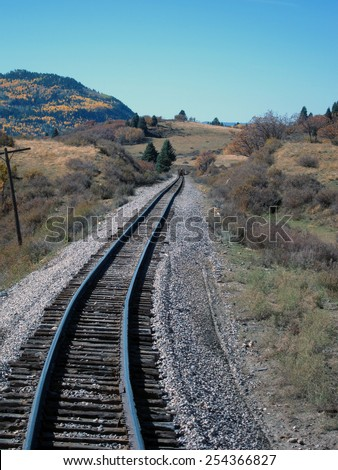 A narrow-gauge railroad track heads toward the horizon through pasture land and past a mountain covered with aspen trees in bloom                                - stock photo
