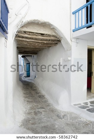 A narrow street in the Greek island going under the arch - is typical for Greece and the Greek Islands - stock photo