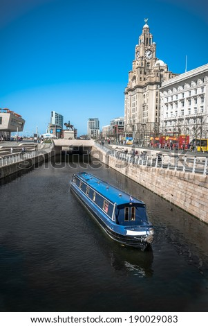 A narrowboat crusing along the Liverpool central canal link at Pier Head with the Liver Building and ferry terminal in the background. - stock photo