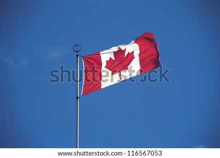 A national flag of Canada against blue sky - stock photo
