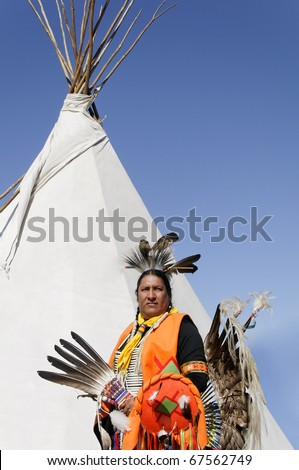 A Native American in ceremonial costume and teepee. - stock photo