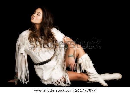 A Native American woman in her traditional dress, looking over her shoulder. - stock photo