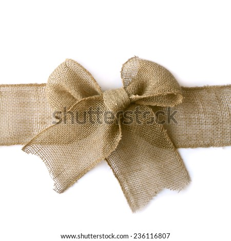 A natural colored burlap ribbon is tied in a bow as if wrapped around a Christmas present, isolated on a white background, with vertical copyspace - stock photo