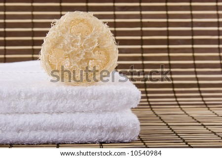 a natural sponge and two white towels - stock photo