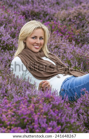 A naturally beautiful young blond woman in a field of purple heather flowers - stock photo