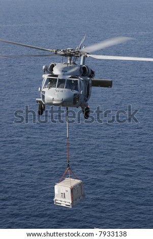 A Navy SH-60 Helicopter Performs Replenishment At Sea On a Nuclear Aircraft Carrier - stock photo
