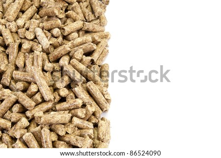 A neat edge of wood pellets pile, isolated on white. - stock photo
