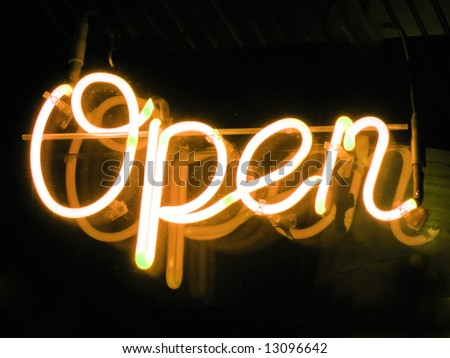 A neon orange OPEN sign glowing in the window of a restaurant. - stock photo
