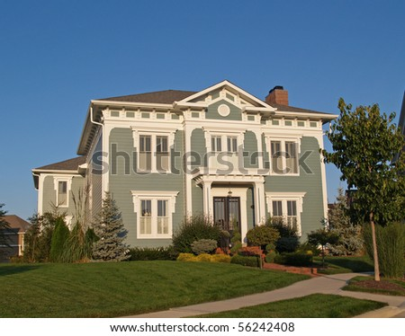 A new home constructed to look like an old two story historical home with green siding and white trim. - stock photo