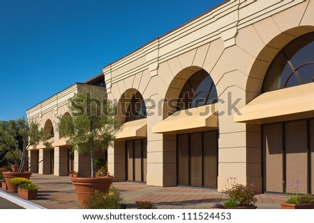 A new office building along a walkway with potted trees and plants. - stock photo