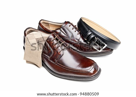 A new pair of brown leather dress shoes with argyle socks and a black belt - stock photo