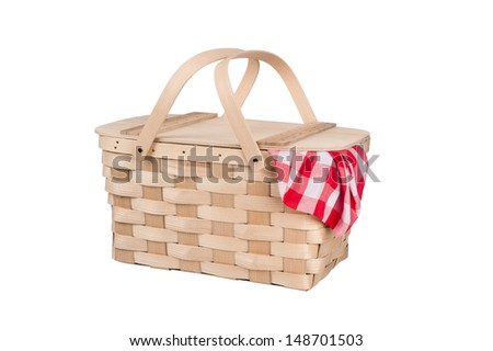 A new wicker and wood picnic basket with a red checkered tablecloth peeking out the side. Isolated on white. - stock photo