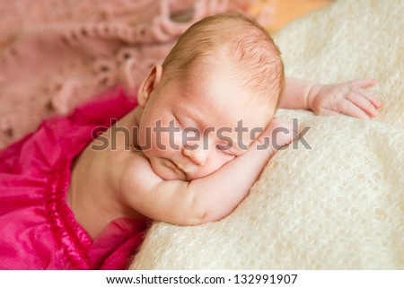 A newborn baby sleeping on a soft white background. Childhood or parenting concept. - stock photo