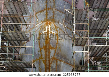 A newly built ship is in dry dock of a shipyard - stock photo