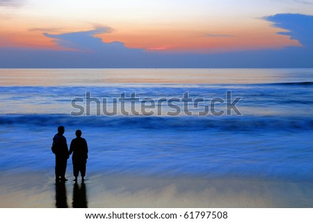 A newly married couple having fun at the beach - stock photo