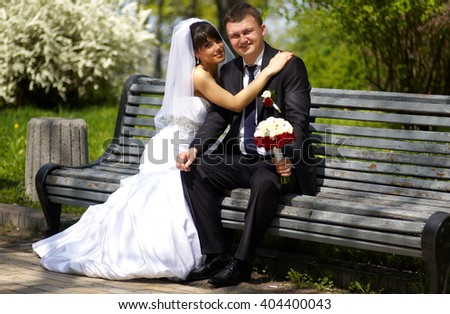 A newly married couple sin on the bench hold hands with bouquet of flowers and look with eyes full of love at each other/Newly wedded couple  - stock photo