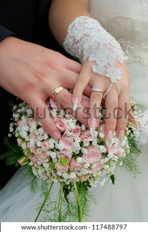 A newly wed couple place their hands on a wedding bouquet showing off their wedding bands. - stock photo