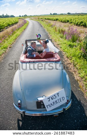 A newlywed couple is driving a convertible retro car on a country road for their honeymoon. They are looking back for the camera - stock photo