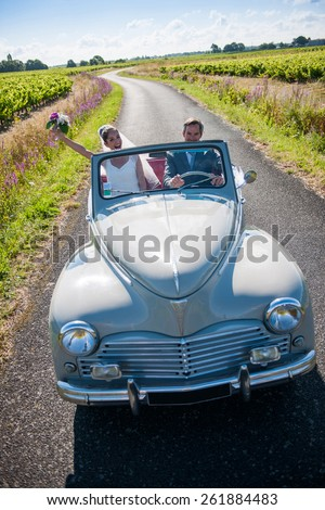 A newlywed couple is driving a retro car on a country road for their honeymoon - stock photo