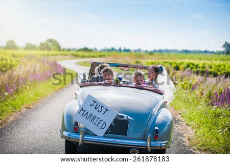 A newlywed couple is driving a retro car on a country road with their two beautiful children, rear view - stock photo