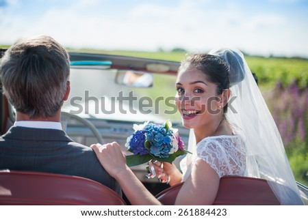 A newlywed couple is driving a retro car, the bride is looking at camera with her bouquet, rear view - stock photo