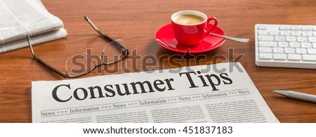 A newspaper on a wooden desk - Consumer Tips - stock photo