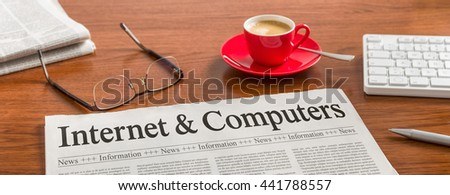 A newspaper on a wooden desk - Internet and Computers - stock photo