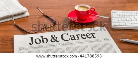 A newspaper on a wooden desk - Job and Career - stock photo