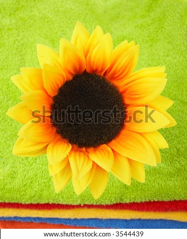 A nice artificial flower on multicolor towels stacked. Shallow DOF - stock photo