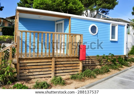 a nice blue mobile home with a wooden veranda in a campsite - stock photo