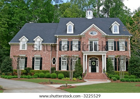 A nice brick two story home with landscaping - stock photo