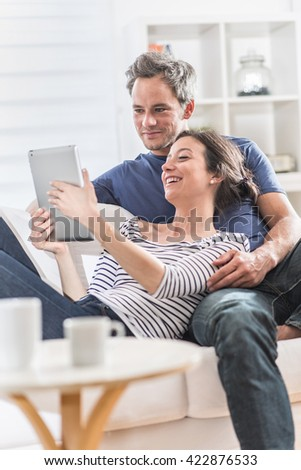 a nice couple at home using a tablet, they are sitting on a white couch, having fun by watching family pictures - stock photo