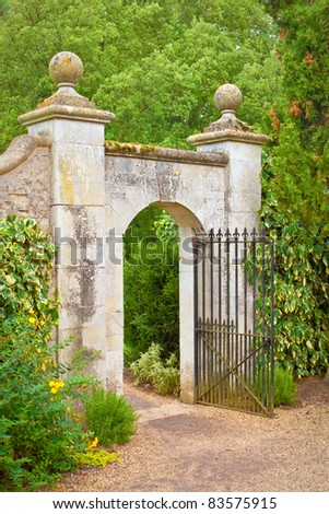 A nice gate in a stone wall in an english garden - stock photo