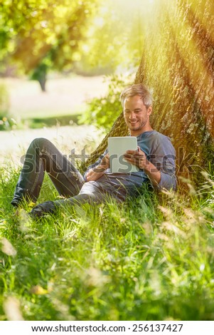 A nice grey hair man is sitting against a tree in the grass, looking at his tablet. He is relaxing, enjoying the shadow of the tree in a sunny day. - stock photo