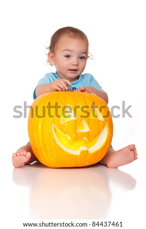 A nice image of a Hispanic baby holding a pumpkin. - stock photo