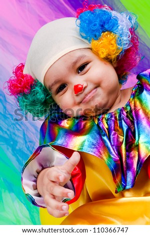 A nice kid wearing clown clothes and hair. The boy is very happy on a colorful background. The toddler is on the floor with some toys. - stock photo