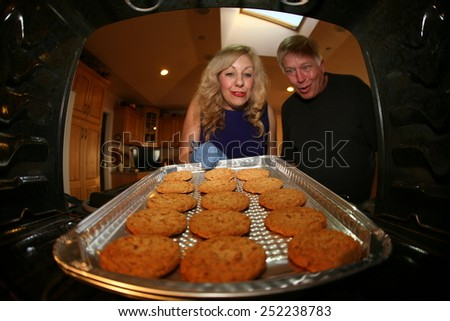 A nice lady bakes Cookies for her favorite plumber as a special Thank You. Shot from inside the oven out for a unique view. Focus on the cookie with the people slightly out of focus. - stock photo