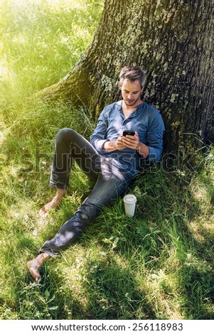 A nice looking grey hair man is sitting against a tree in the grass, looking at his smartphone; his coffee next to him. He is relaxing, enjoying the shadow of the tree in a sunny day. - stock photo