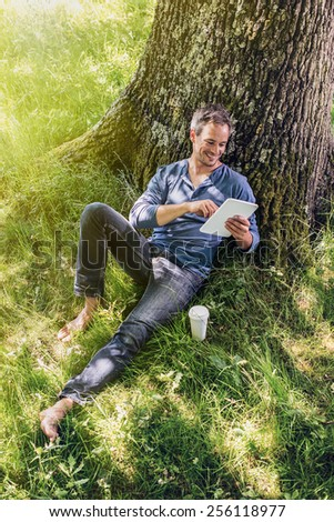 A nice looking grey hair man is sitting against a tree in the grass, looking at his tablet ; his coffee next to him. He is relaxing, enjoying the shadow of the tree in a sunny day. - stock photo