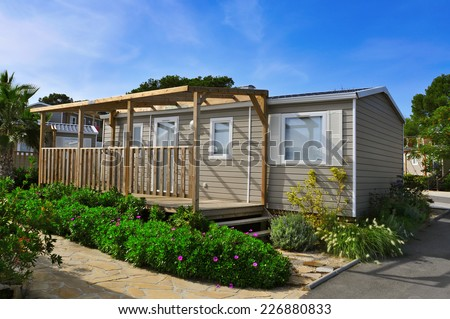 a nice mobile home with a wooden veranda in a campsite - stock photo