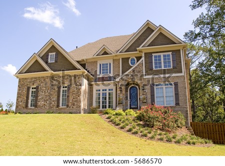 A nice stone and brick house on a landscaped hill - stock photo