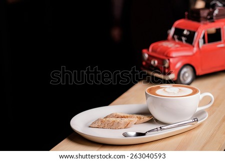 A nice view of capuccino and Italian pastries biscotti near red retro toy car on black background - stock photo