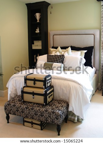 A nicely decorated guest bedroom with a collection of suitcases, a ceiling fan and a padded headboard - stock photo