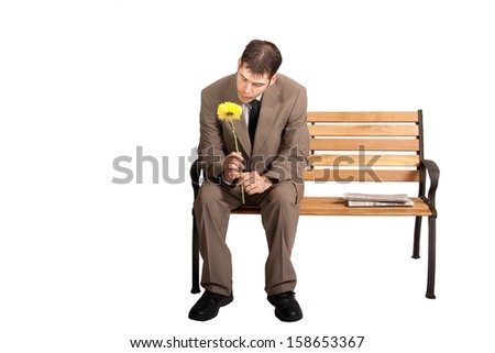 A nicely dressed man stares at a yellow flower while sitting on a park bench. Full length, isolated on white.  - stock photo